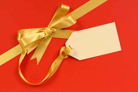 gift ribbon: Red and gold Christmas gift ribbon bow with blank tag or label diagonal