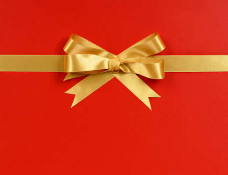 Gold gift bow ribbon horizontal isolated on red wrapping paper background