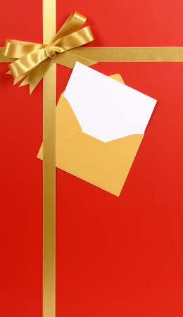 gift ribbon: Red background gold Christmas gift ribbon bow with blank invitation or greetings card vertical