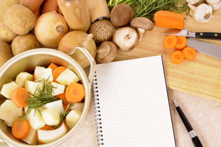 stockpot: Casserole pot with organic vegetables and herbs on kitchen worktop with blank cookbook or recipe book