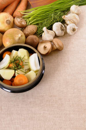 stockpot: Casserole dish with organic vegetables and herbs on kitchen worktop with copy space. Stock Photo