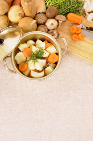 stockpot: Casserole dish or stockpot with organic vegetables and chopping board on linen tablecloth. Stock Photo