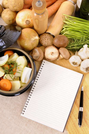 stockpot: Casserole dish or stockpot with organic vegetables and herbs on kitchen worktop with blank cookbook or recipe book Stock Photo