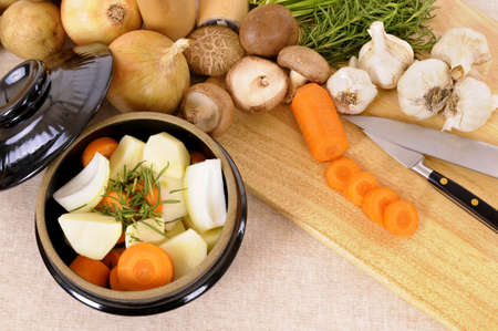 stockpot: Casserole dish with organic vegetables and herbs on linen tablecloth with chopping board.