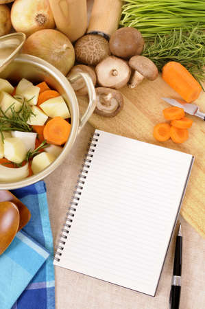 stockpot: Casserole pot with organic vegetables and herbs on kitchen worktop with blank cookbook or recipe book vertical