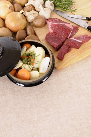 stockpot: Preparing beef for casserole or stew with ingredients and knife on kitchen chopping board.
