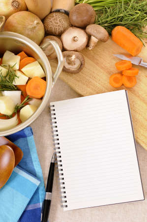 worktop: Casserole pot with organic vegetables and herbs on kitchen worktop with blank cookbook or recipe book vertical