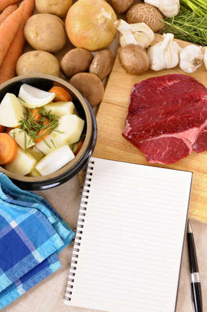 stockpot: Preparing beef casserole or stew with ingredients and herbs on kitchen chopping board and blank recipe book.