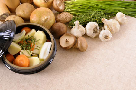 worktop: Casserole dish with organic vegetables and herbs on kitchen worktop with copy space. Stock Photo