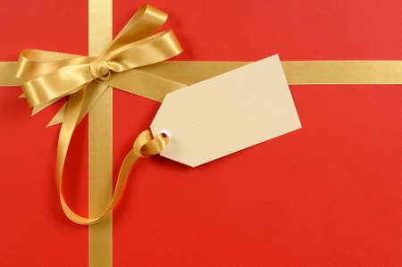 tag: Red gift background, gold ribbon bow, blank gift tag or label, copy space Stock Photo
