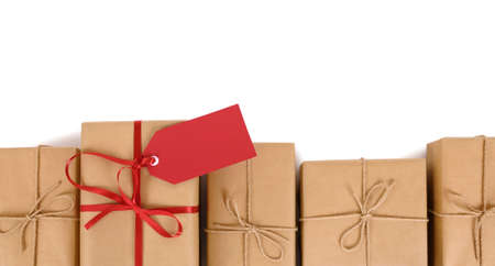 delivery box: Border of brown paper parcels, one unique with red ribbon bow and gift tag or label, isolated on white background