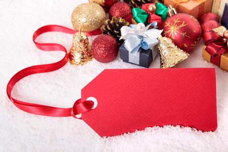 motivos navideños: Etiqueta roja del regalo que pone en un fondo de nieve con diversos regalos y decoraciones de Navidad, espacio de la copia