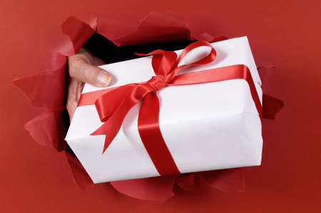torn paper background: White gift with ribbon being delivered through a red torn paper background.