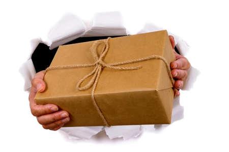 bursting: Man hands delivering or giving parcel through torn white paper background
