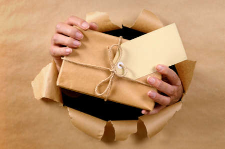 brown paper background: Man hands delivering or giving parcel through torn brown paper background