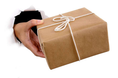 Man hand delivering or giving parcel through torn white paper background Standard-Bild