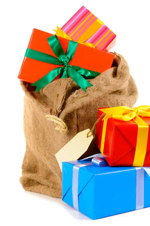sackful: Santa sack or stocking full with pile of Christmas gifts isolated on white background Stock Photo