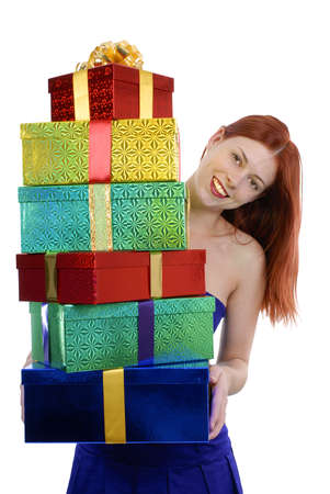 tall: Smiling young adult woman in blue party dress with pile of gifts isolated on white background vertical