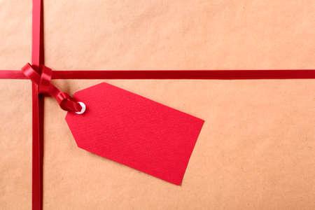 wraps: Etiqueta roja de regalo y cinta, papel de embalaje de paquetes fondo marrón, copia espacio.