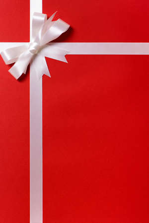 white bow: White ribbon bow, red gift wrap paper background, copy space, vertical Stock Photo