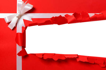 paper rip: Christmas gift torn open strip, white ribbon bow, red wrapping paper background, copy space