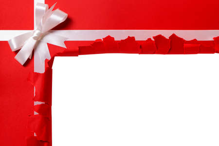 torn: Christmas gift torn open, white ribbon bow, red wrapping paper background, copy space Stock Photo