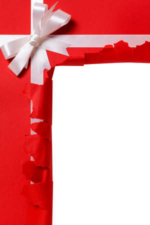 torn: Christmas gift torn open, white ribbon bow, red wrapping paper background, copy space, vertical