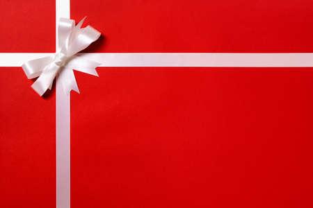 wraps: papel de regalo, lazo de cinta blanca, fondo de papel rojo, el espacio de copia
