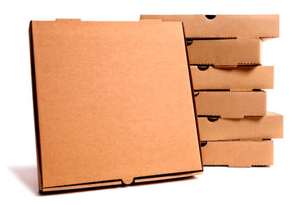 front facing: Stack of plain brown pizza boxes with one front facing box for display or advertising.  Isolated on white background.  Copy space.