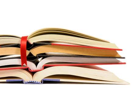 libros abiertos: La pequeña pila de libros abiertos con la cinta marcador rojo sobre fondo blanco