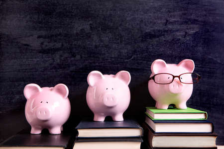 college fund savings: Three piggy banks with blackboard