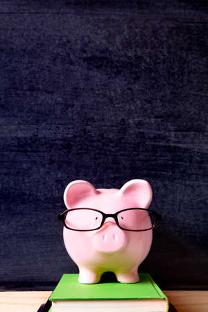 college fund savings: Piggy bank with glasses and blackboard
