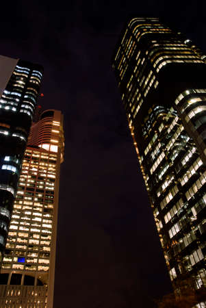 low angle view: Tall skyscraper buildings at night, low angle view