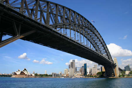low angle views: Sydney harbour bridge looking up from under with financial district and opera house in distance Editorial