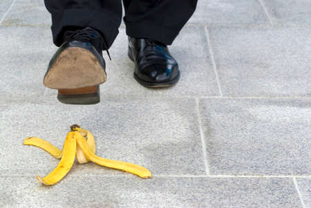 banana skin: Businessman stepping on banana skin, copy space