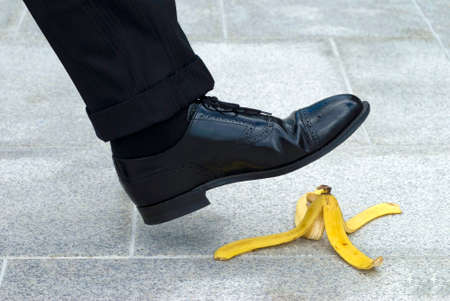 banana skin: Businessman stepping on banana skin Stock Photo