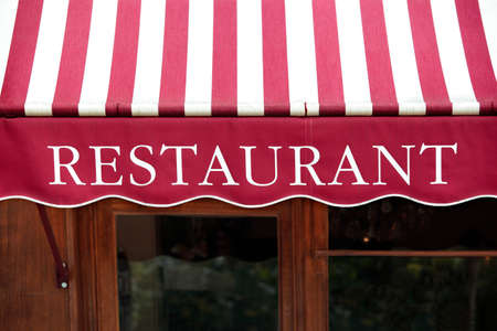 front view: Striped french restaurant canopy in Paris france.