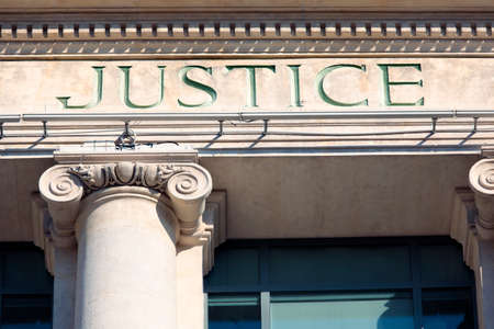 outside house: Justice sign on a Courthouse Building.