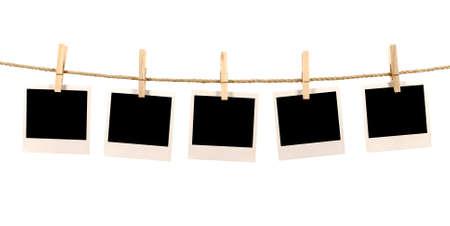 Mehrere leere polaroidart instant Bilderrahmen Druck auf einem Seil oder Wäscheleine hängen, weißer Hintergrund Standard-Bild