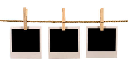 string: Several blank polaroid style instant photo print frames hanging on a rope or washing line, white background