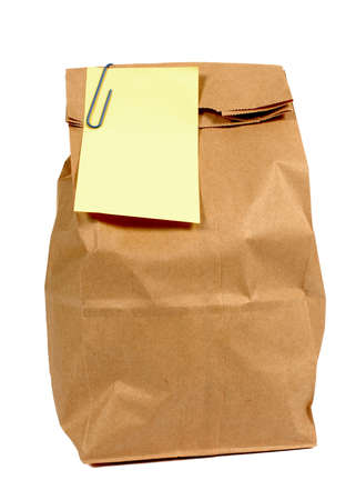postit: Brown paper lunch or groceries bag with yellow post it style sticky note isolated on white