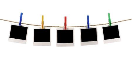 Varios marcos de impresión instantánea de fotos de estilo polaroid en blanco colgando de una cuerda o línea de lavado, fondo blanco