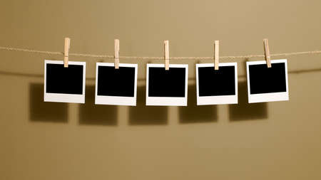 Polaroid style instant photo prints hanging on a rope or washing line with darkroom wall background