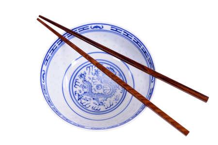 Classique motif bleu vide chinois bol de riz avec des baguettes en bois isolé sur fond blanc Banque d'images