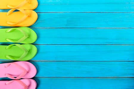 flipflops: Side border row of flip-flops on blue background wood beach decking