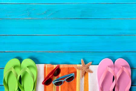 flops: Summer beach objects border, sunglasses, flip flops, copy space