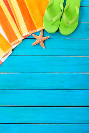 Summer beach objects border, flip flops, copy space, vertical, blue background
