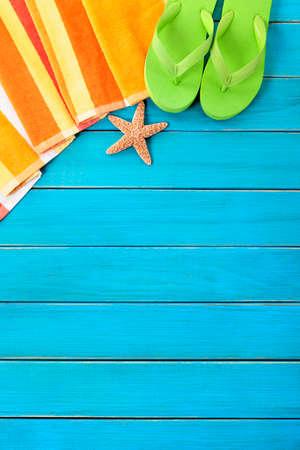 Summer beach objects border, flip flops, copy space, vertical, blue background