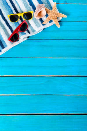 towel beach: Summer beach background border, sunglasses, towel, starfish, blue wood decking, copy space, vertical