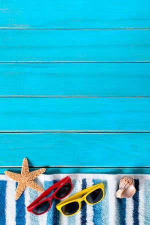 background summer: Summer beach background border, sunglasses, towel, starfish, blue wood decking, copy space, vertical